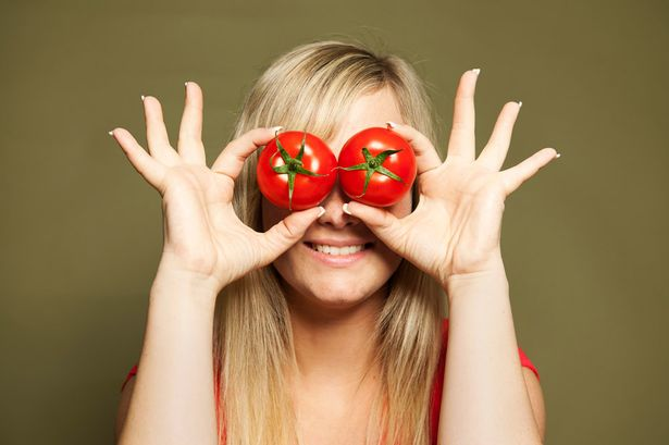 Young-woman-holding-tomatoes
