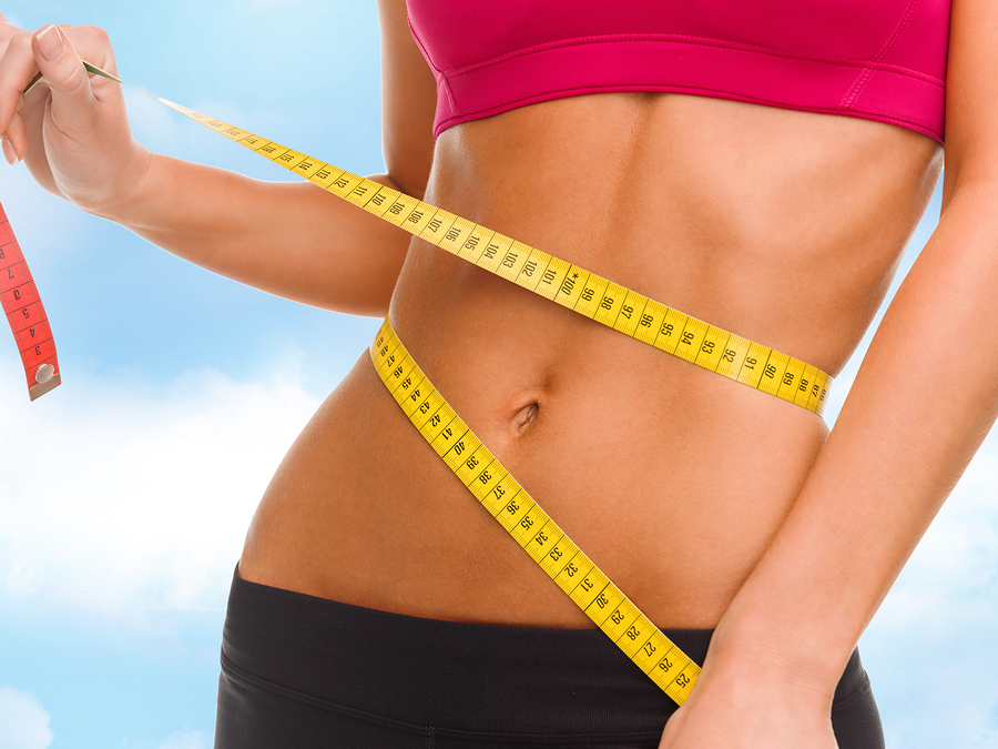 sport, fitness and diet concept - close up of trained belly with