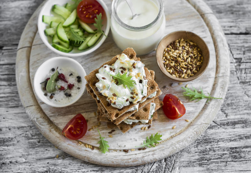 healthy-snack-rye-crackers-cottage-cheese-cucumber-flax-seed-light-wooden-background-57467743